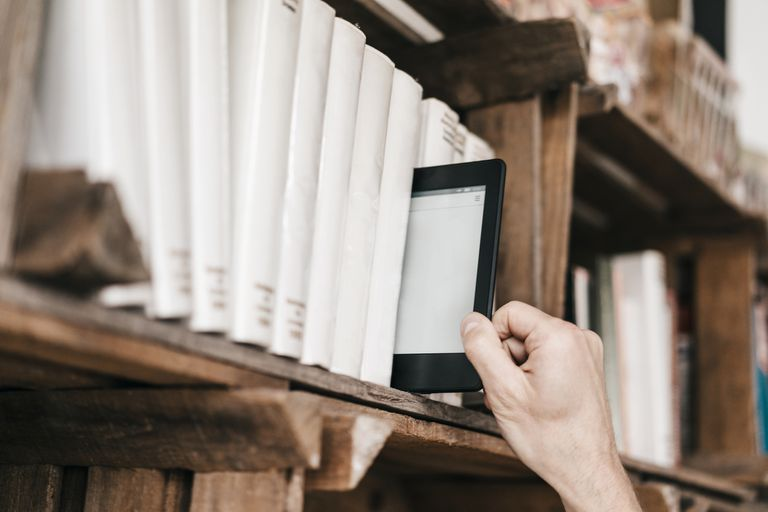 A Kindle among books being pulled off of a shelf.
