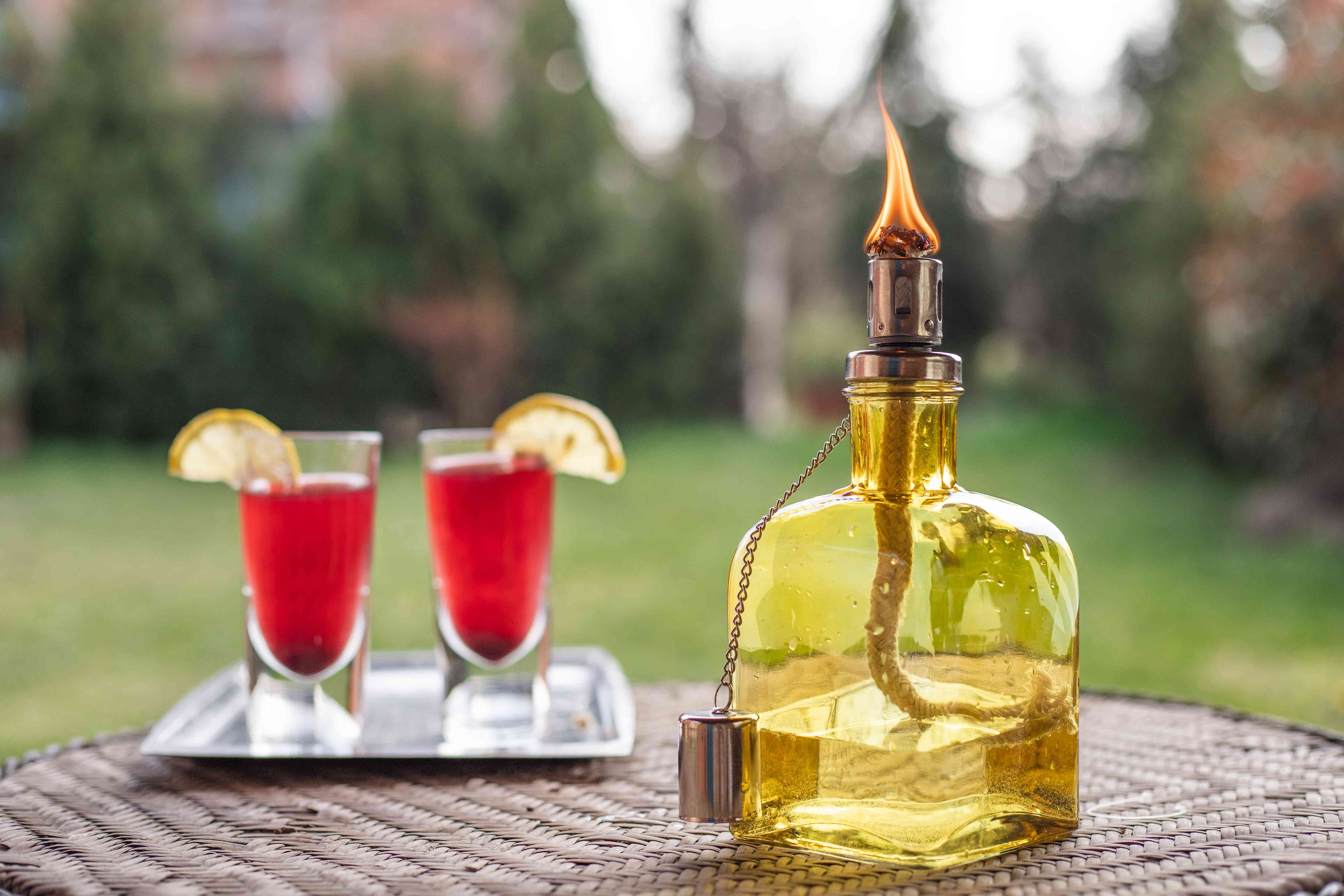 glass bottle turned into lit tiki torch on patio table in backyard with festive drinks