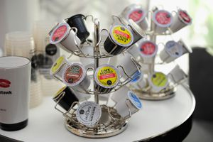 A three-tiered circular rack holding a variety of coffee pods