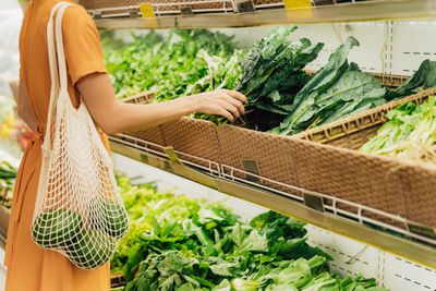 Girl is holding mesh shopping bag with vegetables without plastic bags at grocery shop.
