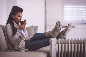 Woman relaxing near an electric space heater.