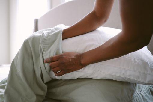 Woman putting pillow in pillowcase