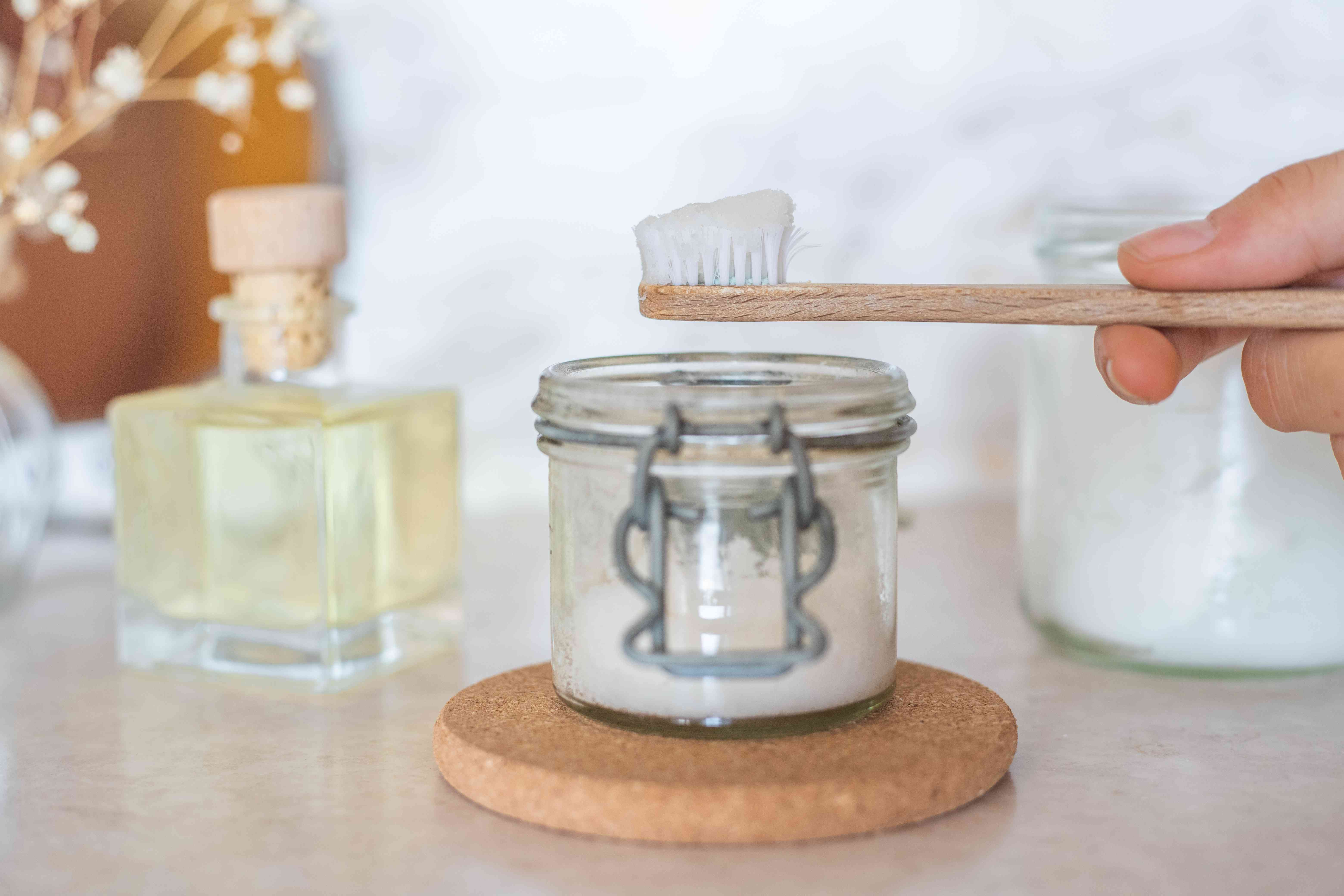 hand holds bamboo toothbrush above glass container of diy baking soda toothpaste