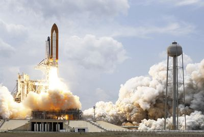A space shuttle lifts off from its launch pad.