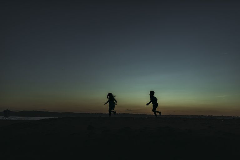 Sihouette of brother and sister running towards ocean at dusk