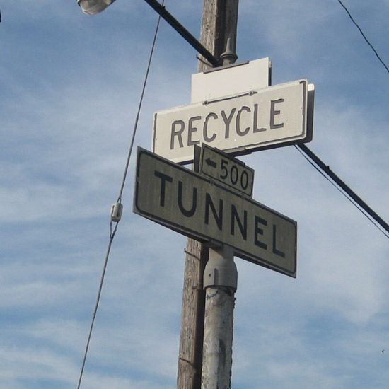 Signs that show recycle and tunnel directions at a dump.