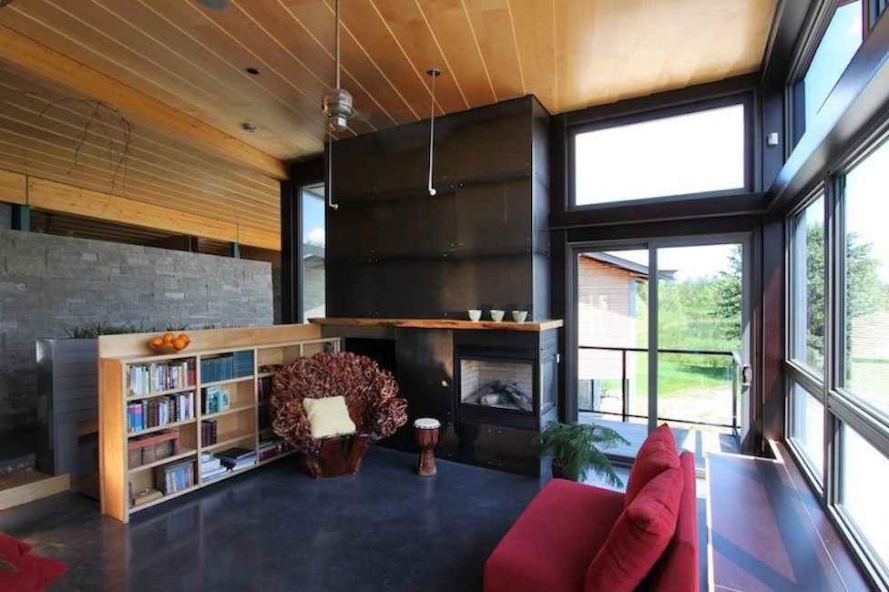 Living room with floor to ceiling windows on one wall, a black fireplace, and a bookshelf