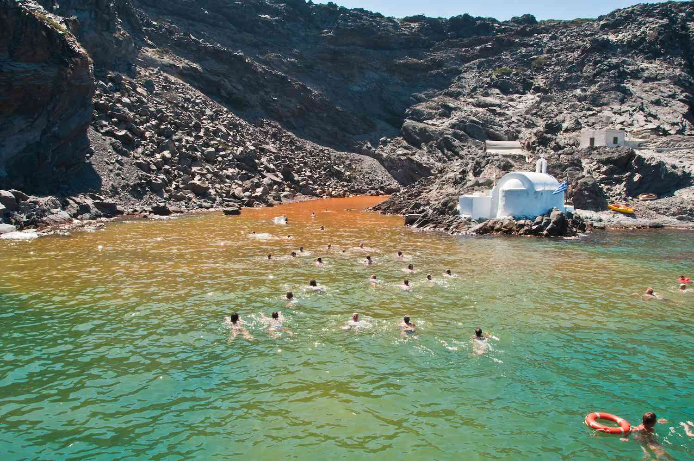 People swimming in the waters on the volcanic island Palea Kemini