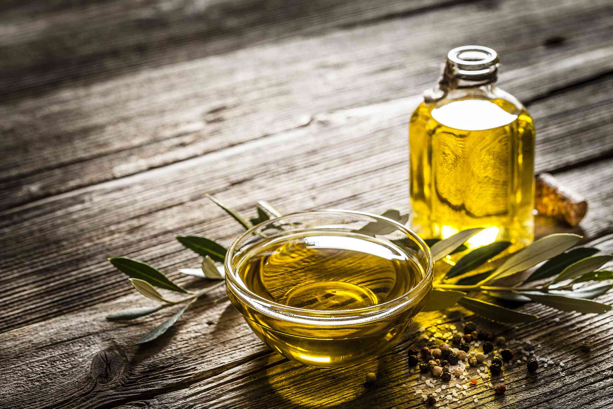 A glass dish full of olive oil beside a bottle on a rustic table.