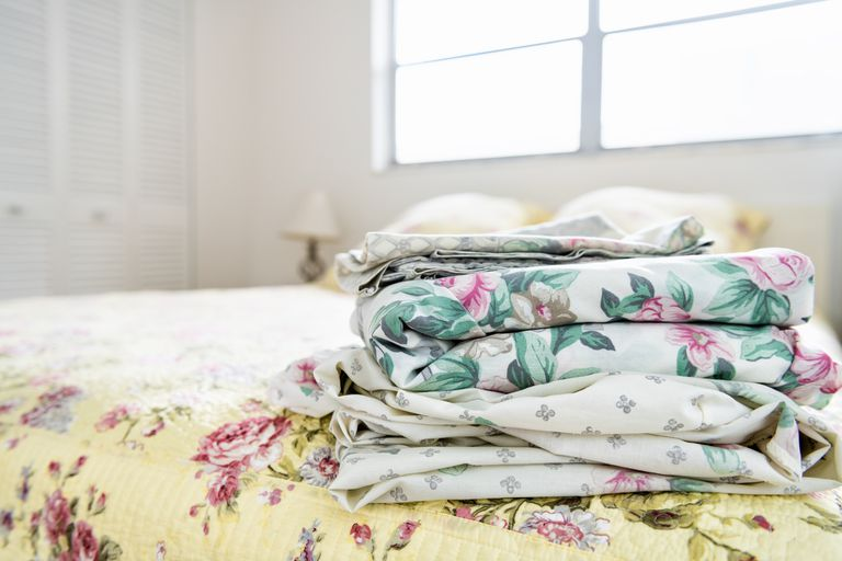 Stack of bedroom linen with floral, flower pattern on top of bed with quilt, quilted comforter, duvet