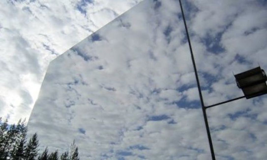 Mirrored siding reflecting blue sky and clouds