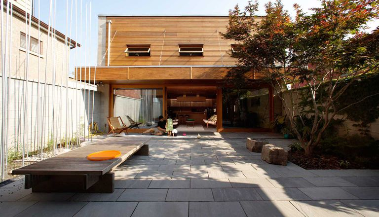 House with a gray stone courtyard in the foreground