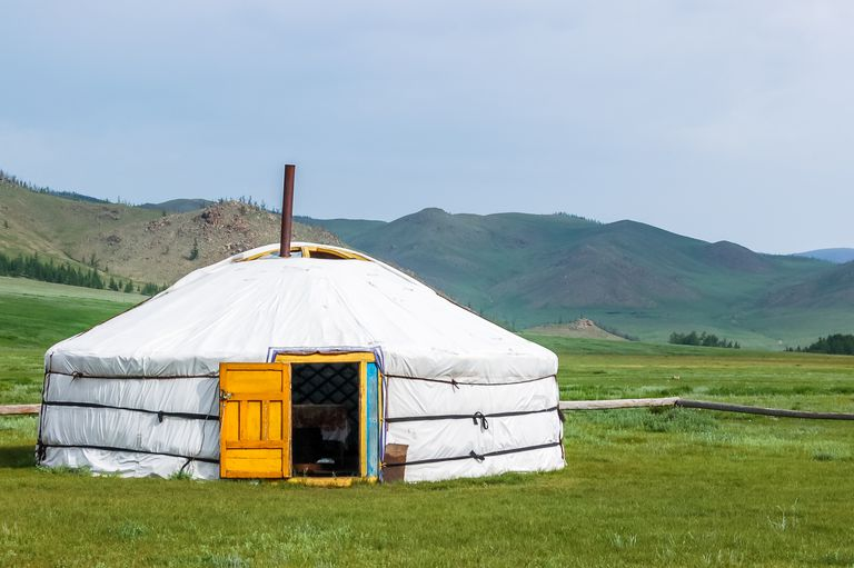 A yurt set up in a field surrounded by hills.
