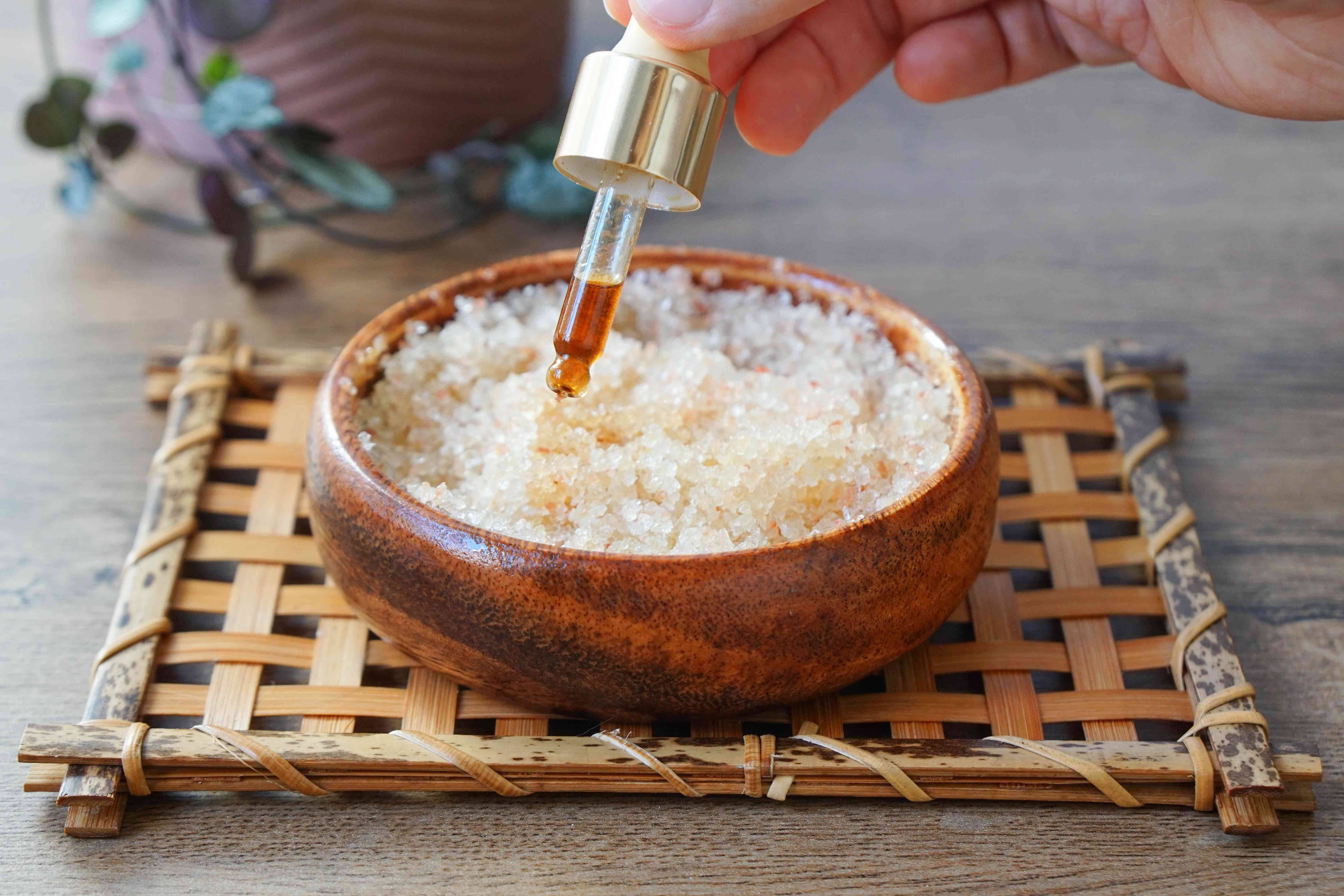 glass dropper of essential oil is added to salt scrub mixture in wooden bowl