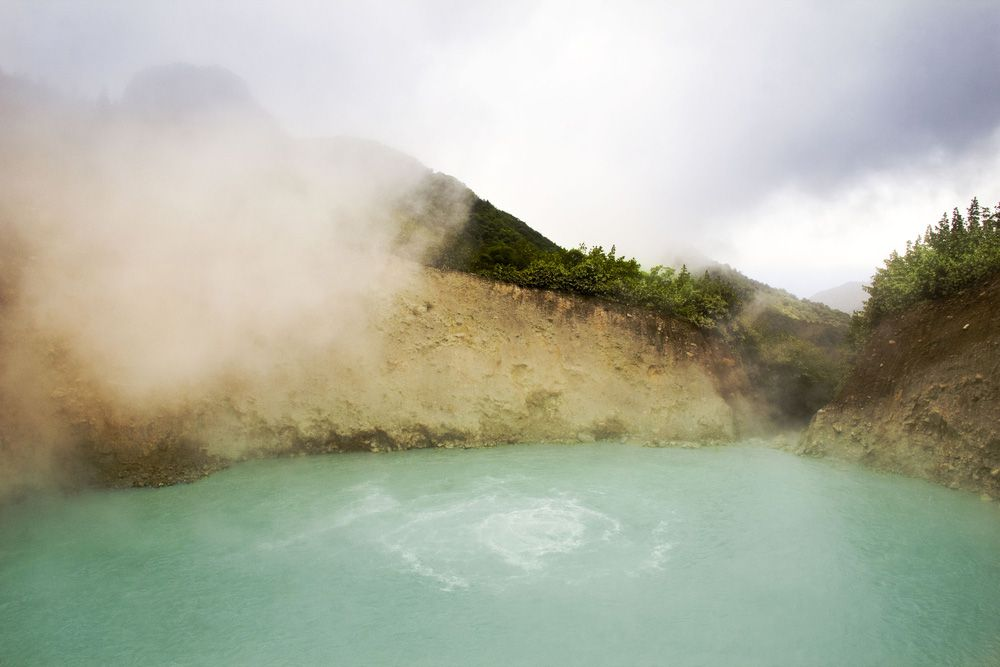 Steam rises from a pool of pale blue water