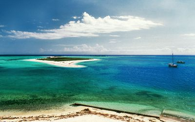 aerial view of bright white sand surrounded by shallow, blue and turquoise waters of one of the small islands of Dry Tortugas with two boats just offshore