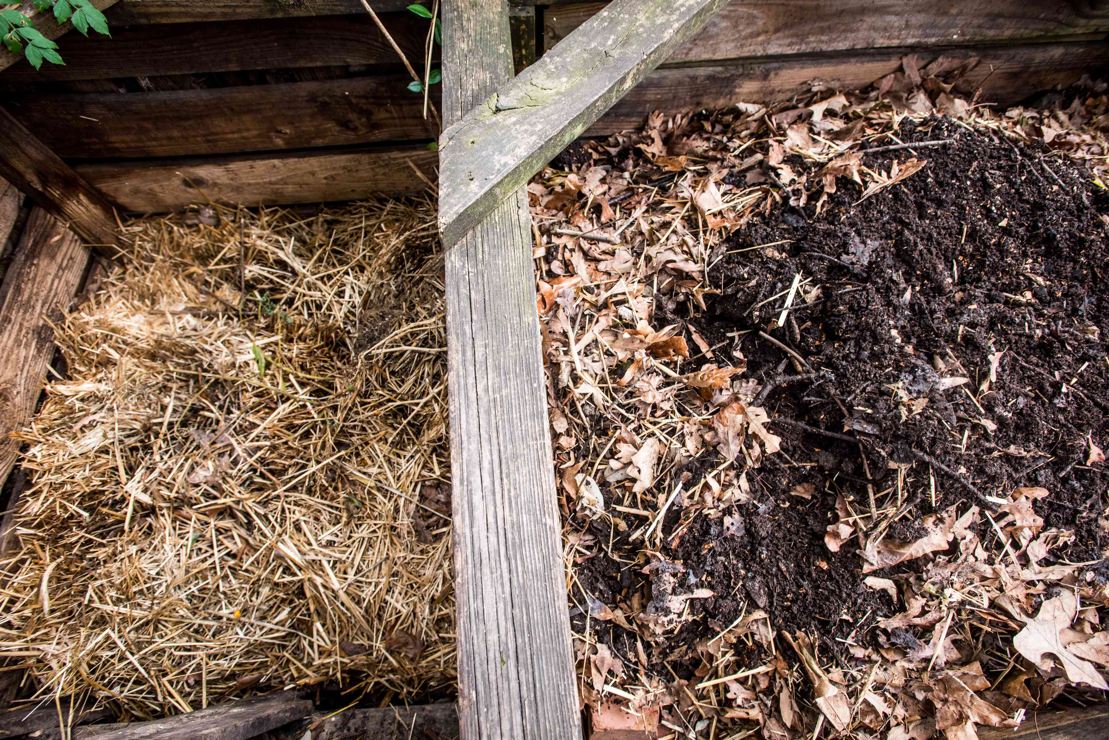 side side shot of compost bin with dirt and hay