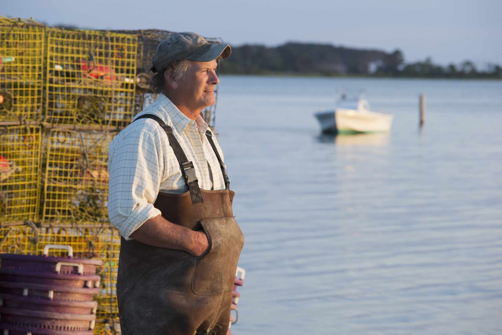 A white old fisherman against cages looking at the bay.