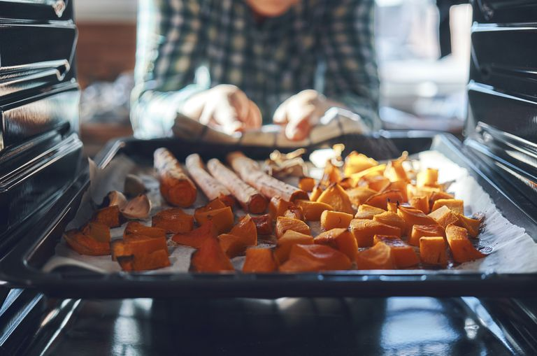 Roasted vegetables being removed from the oven