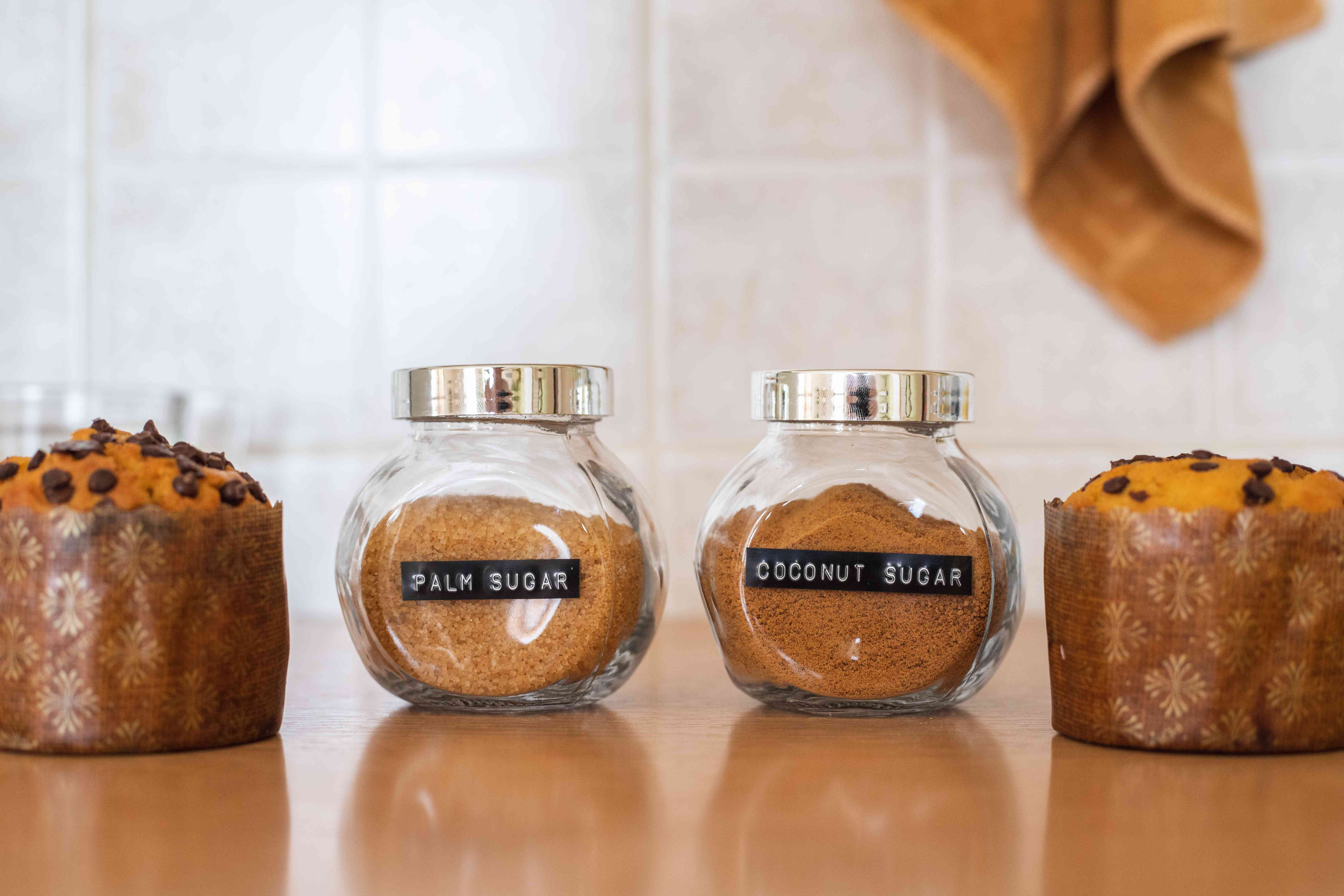 glass dispensers of brown coconut and palm sugars next to chocolate chip muffins