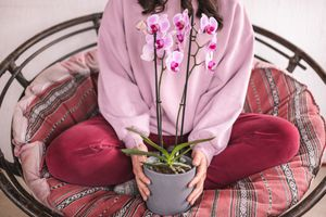 woman in purple sweats poses with purple orchid in large circle chair
