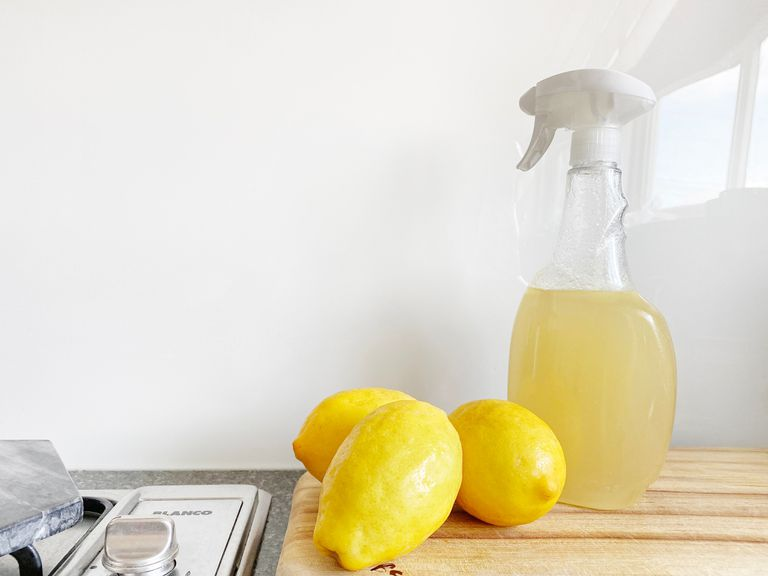 3 lemons next to a spray bottle filled with light yellow liquid on a countertop