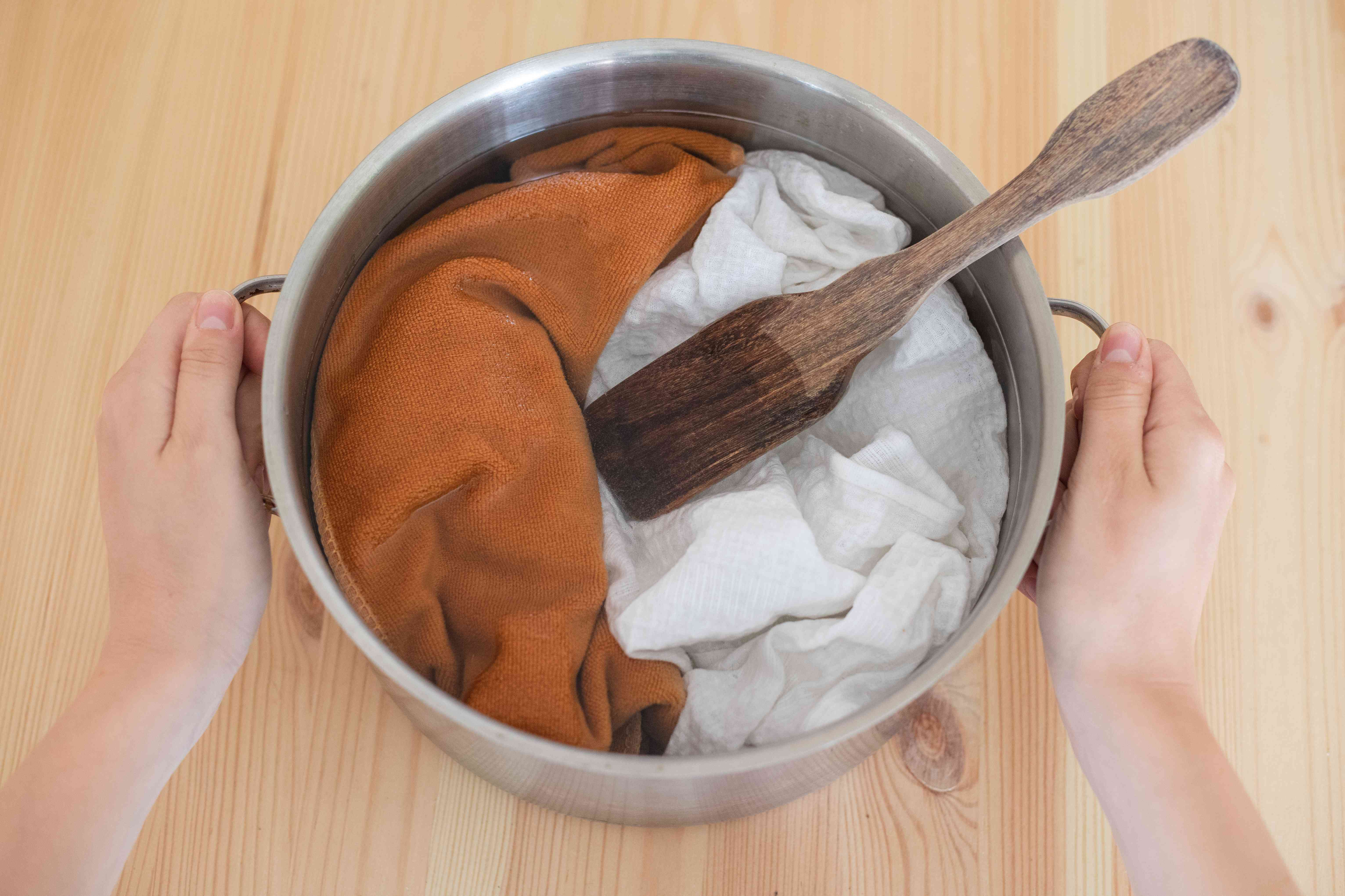 clothing soaks in vinegar water mixture in steel stockpot with hands holding sides