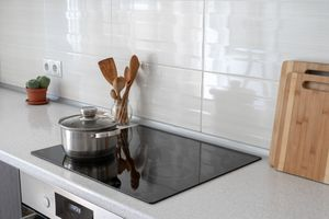 Counter top with built in induction stove top, cutting boards, wooden utensils, and a cactus on the counter