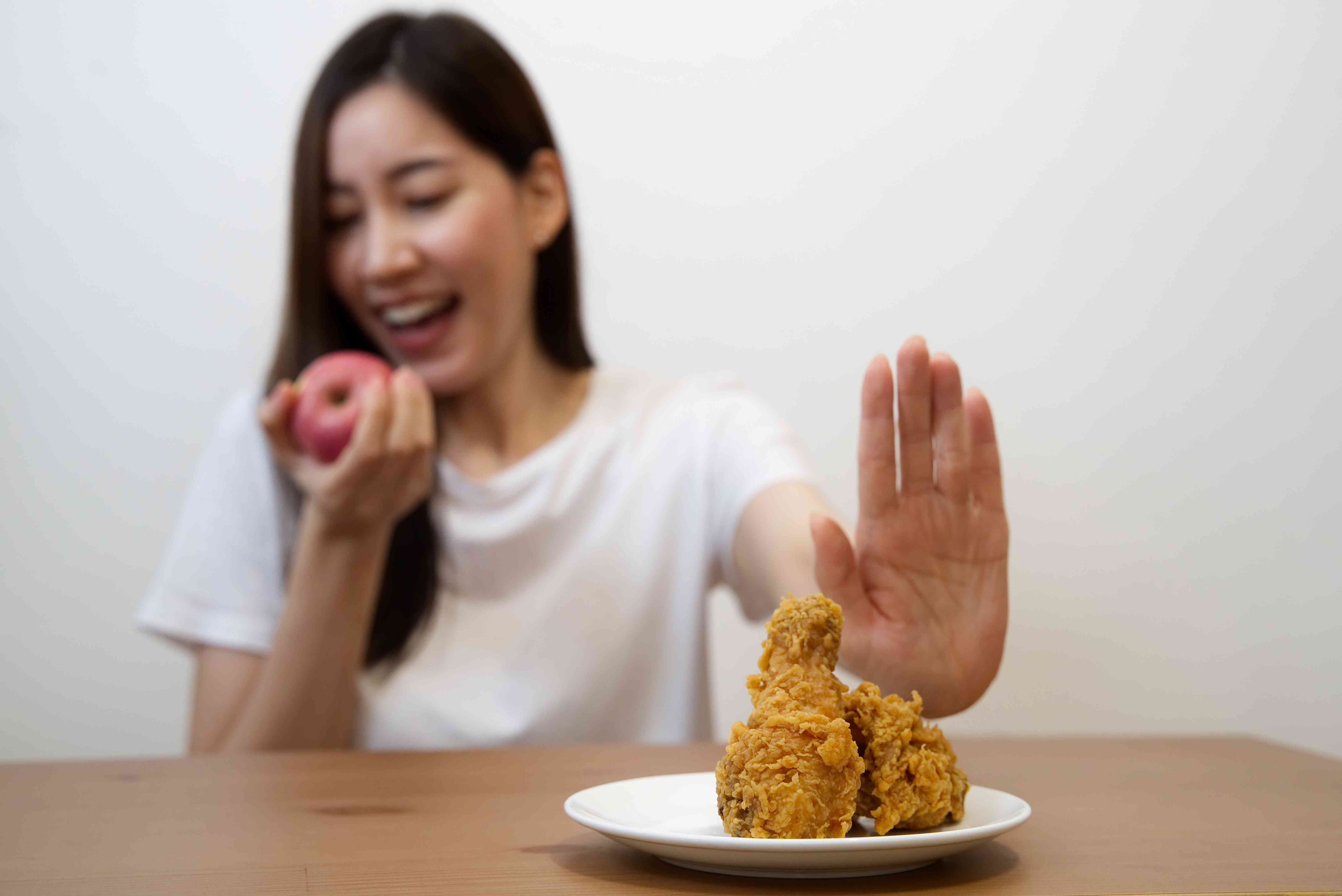 Young girl on dieting for good health concept. Close up female using hand reject junk food by pushing out her favorite fried chicken and choose red apple and salad for good health.