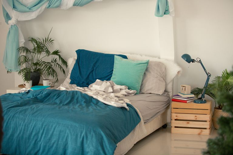 Unmade bed with plants in the corners of the room