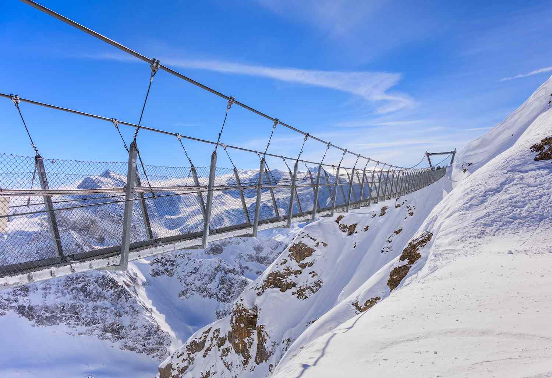 A steel-cable bridge crosses a snowy mountain landscape