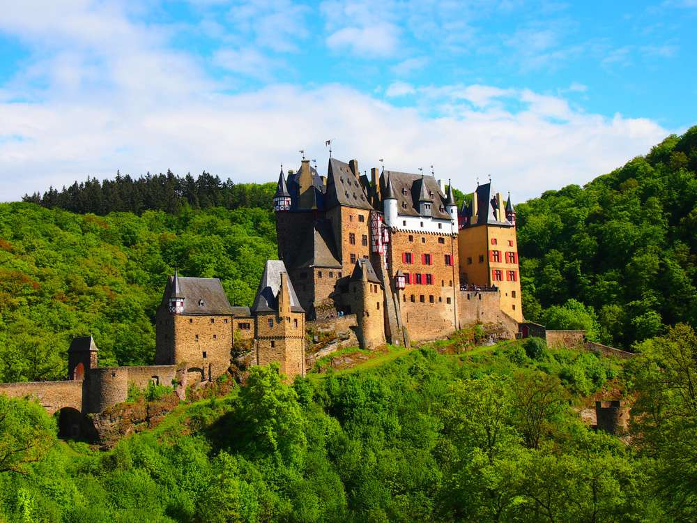 Burg Eltz, a castle on a hill surrounded by lush green foliage under a blue sky with white clouds