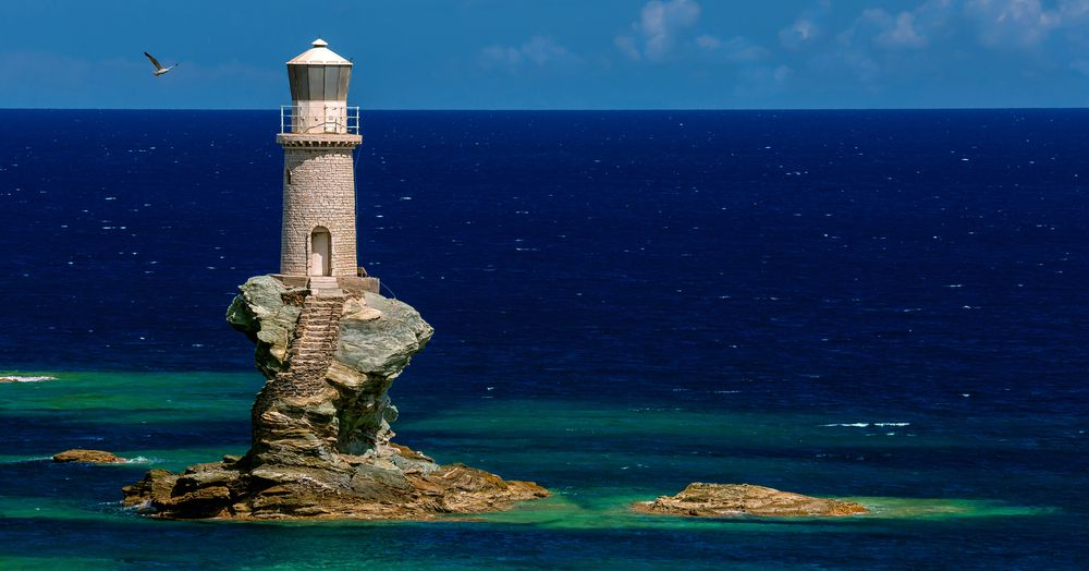 The Tourlitis Lighthouse in Andros, Greece on a bright blue day