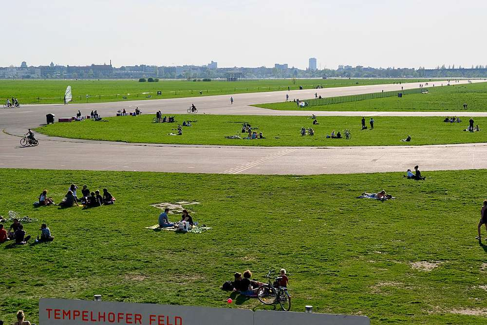 Park visitors sit in the green fields of the former Tempelhof Airport in Berlin