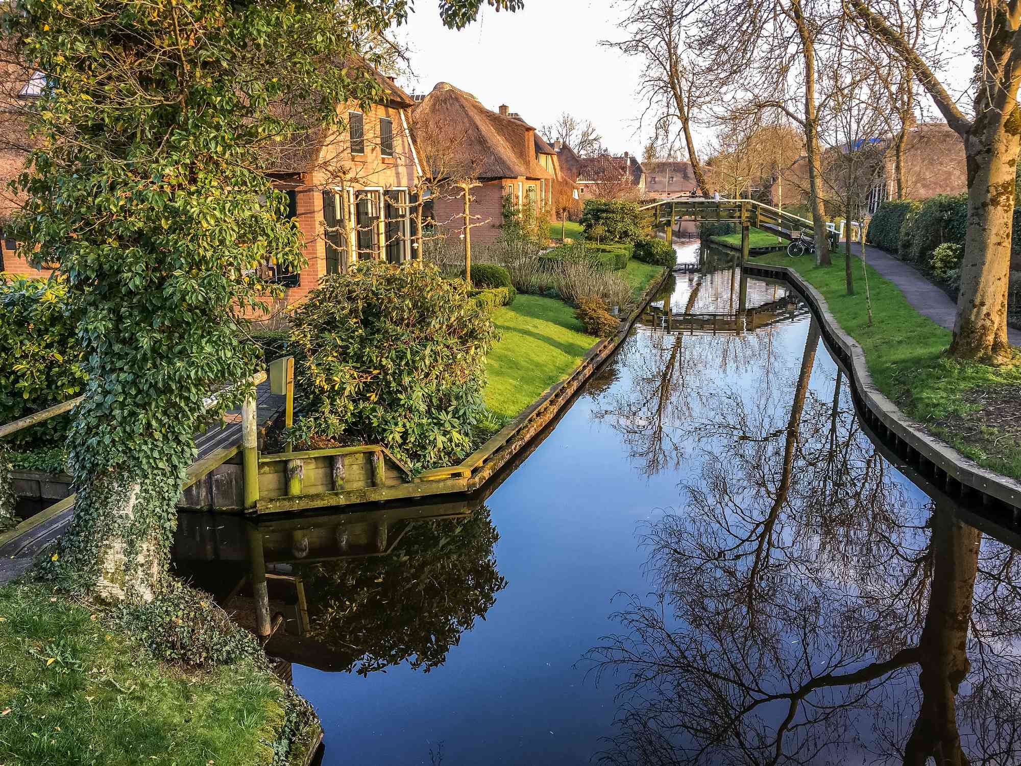 Canal in a residential area with homes and trees along the water in Giethoorn
