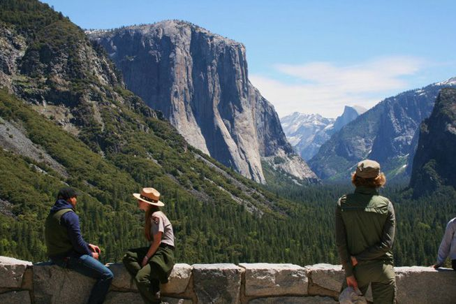 Tourist and a park ranger at a scenic overlook in Yosemite National Park