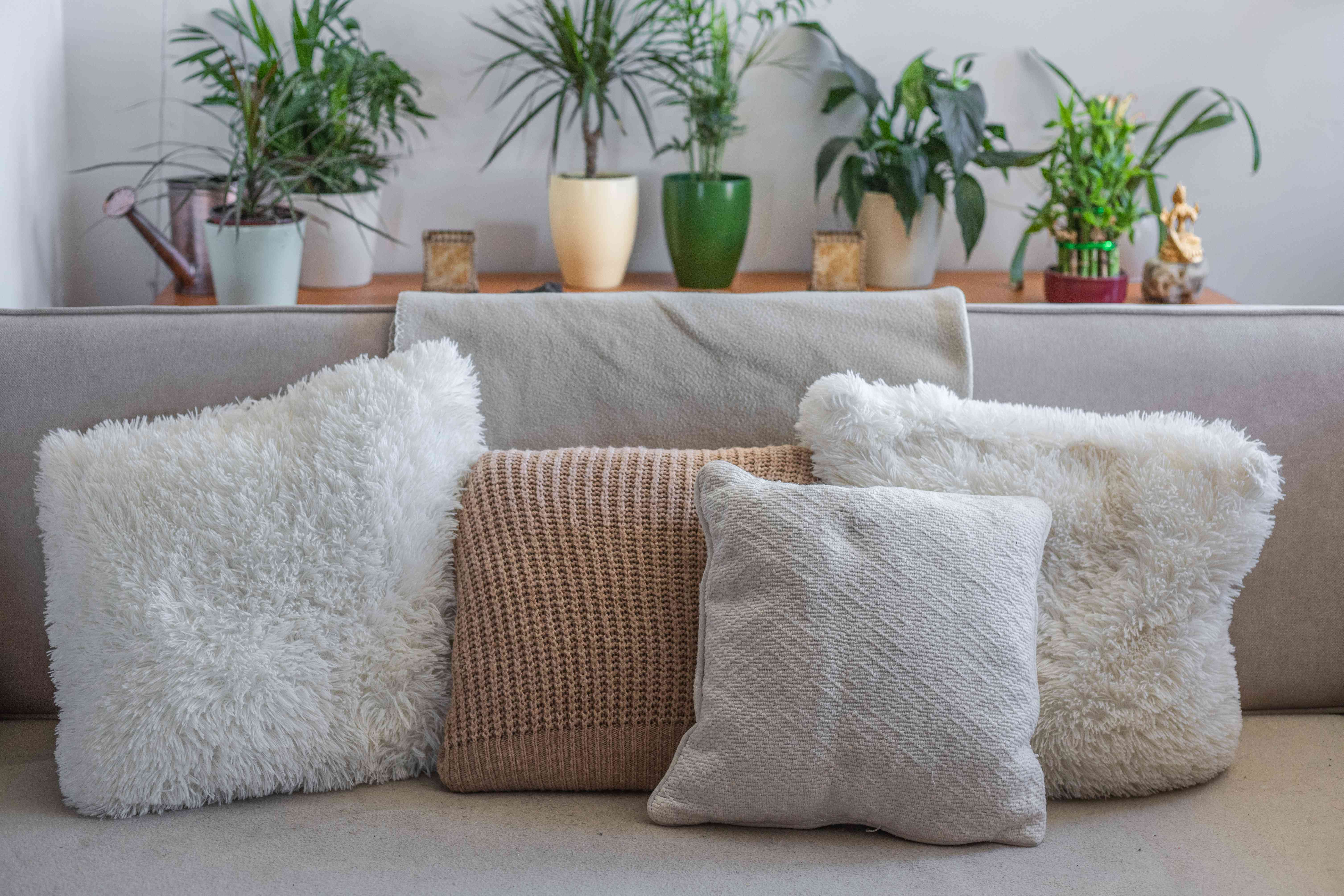 repurposed chunky sweaters turned into pillowcases arranged on couch with plants in background