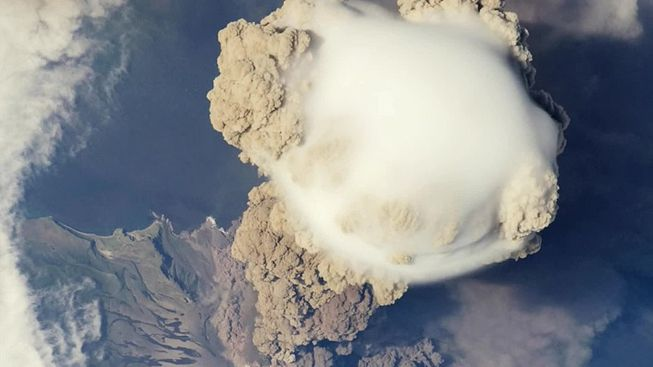 A pileus cloud appears over a volcanic cloud produced by Sarychev Peak
