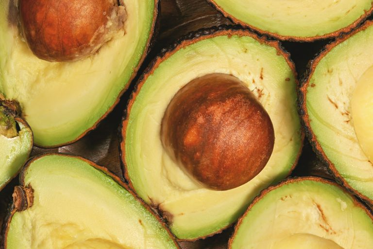 Halved avocados with pits