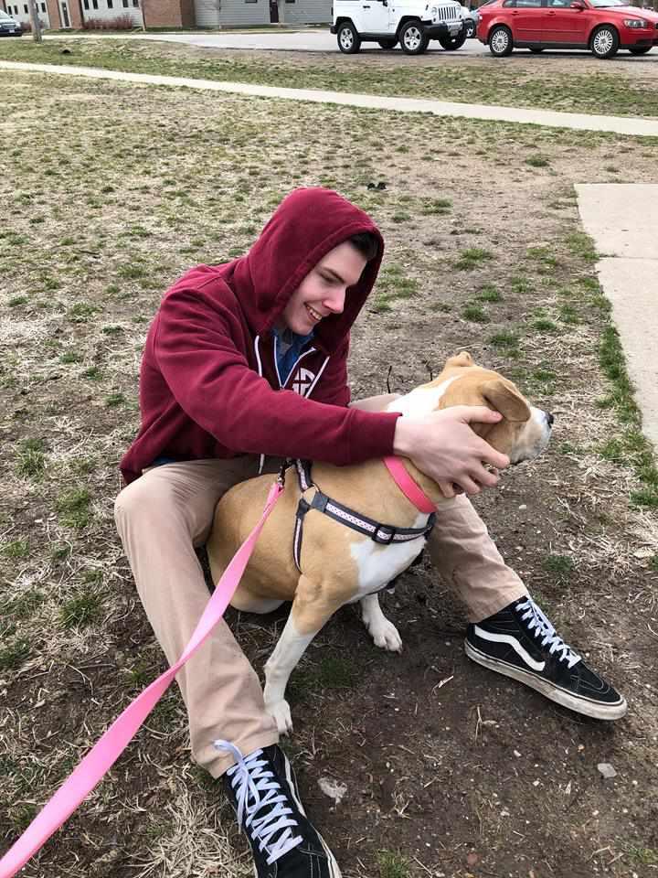 A teen hugging a dog