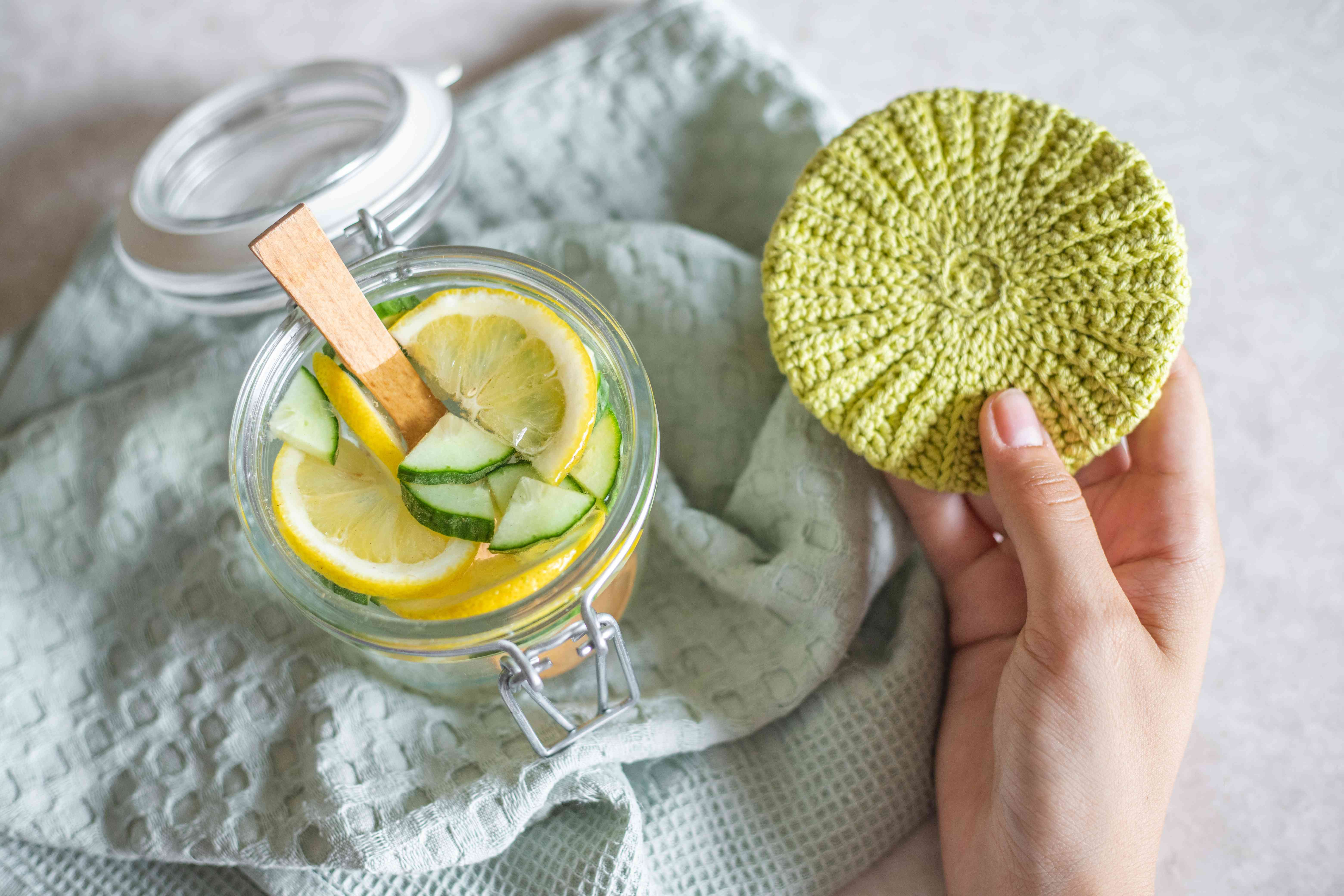 diy cucumber and lemon slice toner in glass lidded jar next to hand with homemade scrub