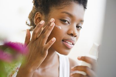 Black woman putting on face lotion - stock photo