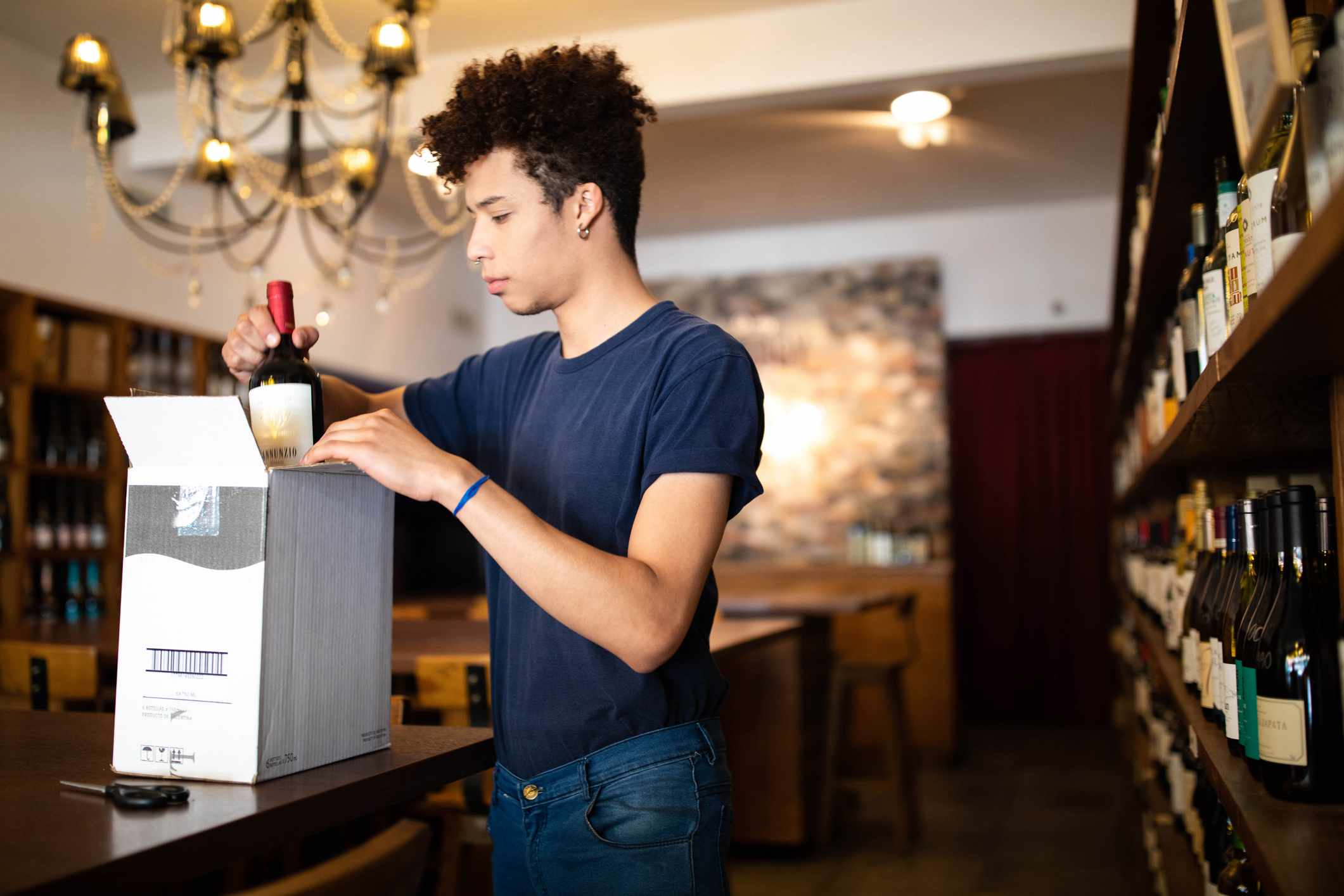 A young man unpacks wine in a shop.
