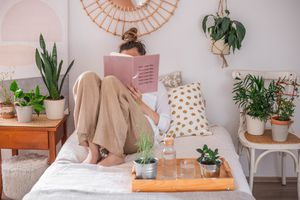 woman reads book in bed surrounded by various plants on chairs and trays