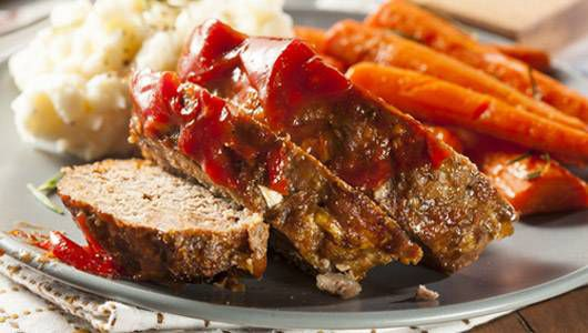 Ground Beef Meatloaf on a plate with carrots and potatoes.