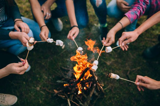A group a teenagers making s'mores