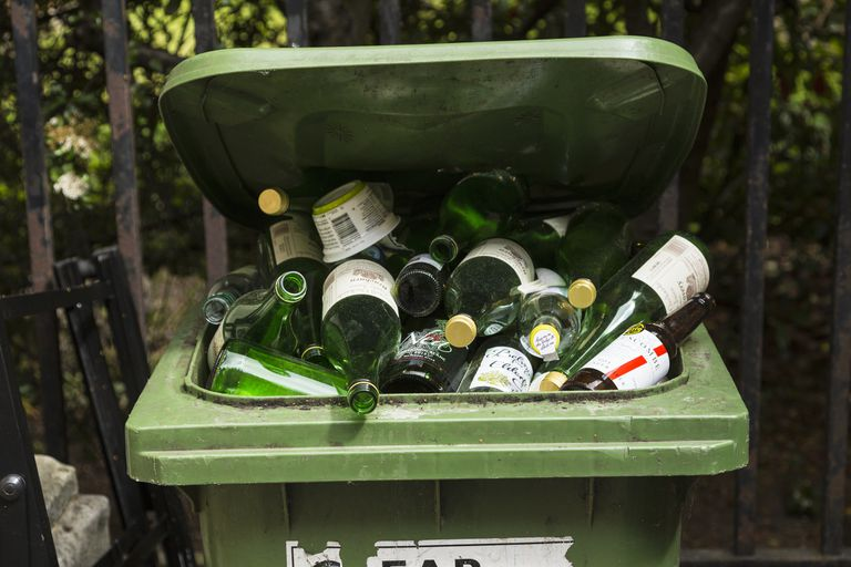 Glass bottles piled up in a recycling bin.