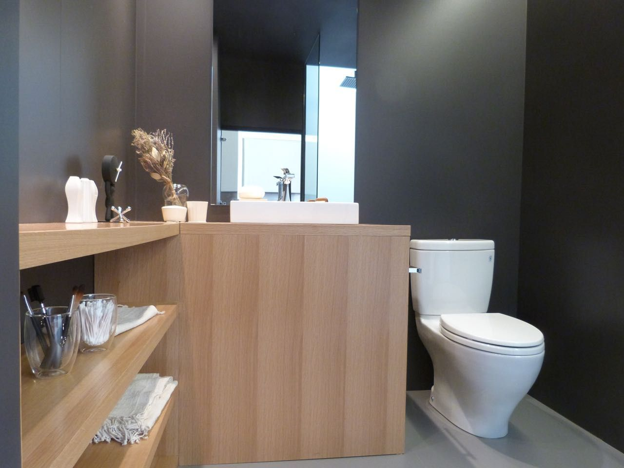 Bathroom with a toilet, a pale wood counter, and shelving visible