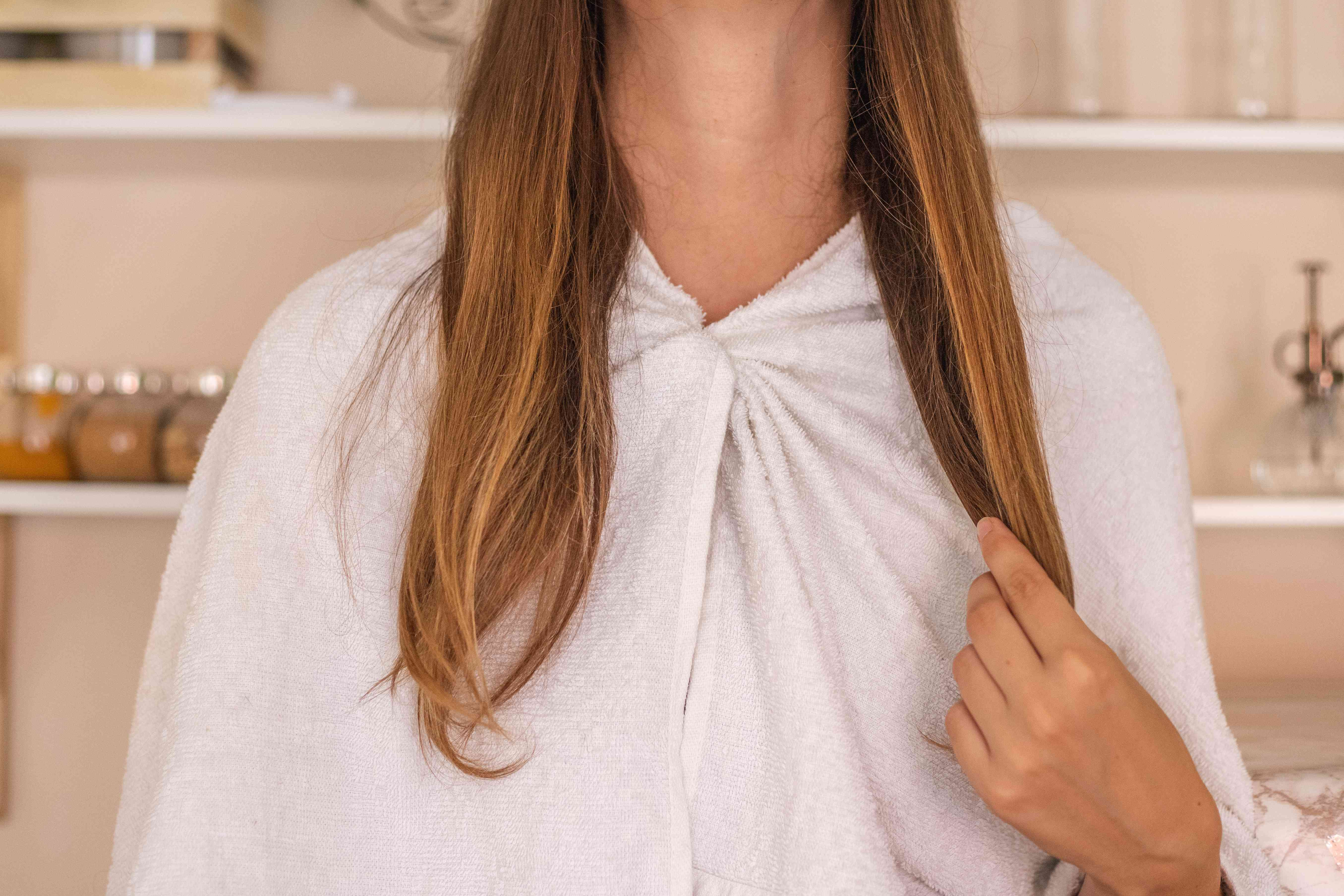 woman with towel wrapped around shoulders applies olive oil mask to ends of long hair