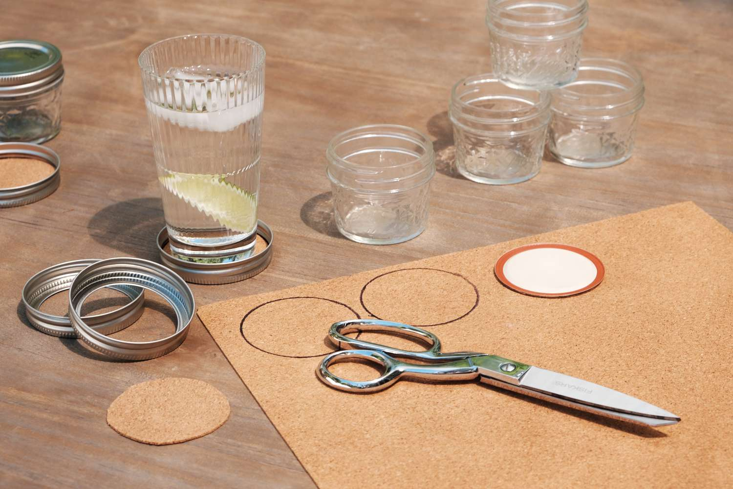 scissors and cork material to make DIY coasters with old canning lids
